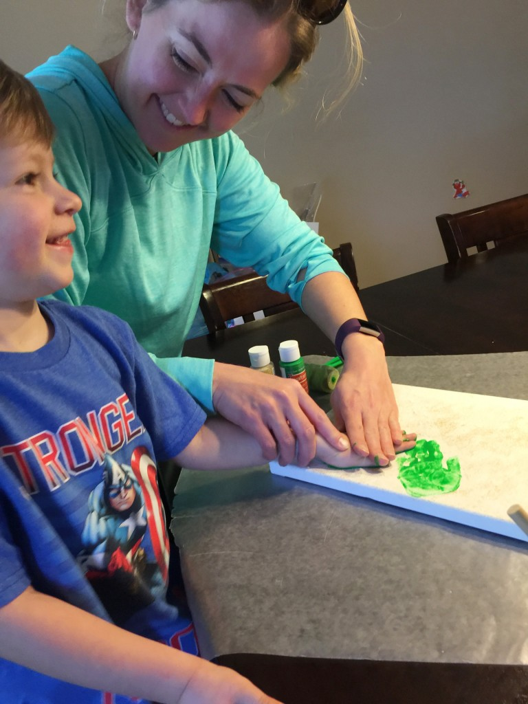 a mother and son painting a craft
