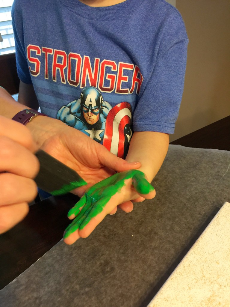 Painting a child's hand for a st. patrick's day craft.